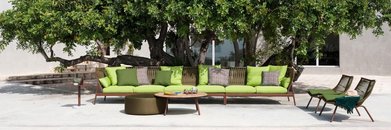 hauser-design-roda-sofa-piper-mit-braunen-baendern-und-gruenen-kissen